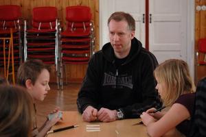 LÄRORIKT. Trollkonstnären Magnus Vihagen visar ett trick med siffror. Felix Hallgren, 11 år, och Tilde Byström, 10 år, suger in kunskapen.