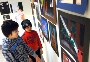 Bilderna som årskurs 9 skapat fångade Mohammed Nehad och Said Alis intresse. Kulturskolans utställning finns i bibliotekets utställningslokal.