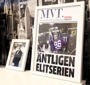 Lokaltidningen MVT:s löpsedel från Motalas återkomst till elitserien står inramad på TV-bänken hos Viktor Spångberg. På bilden syns när lillebror Anton häller champagne över Viktor med tröja 96.