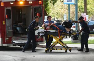 En skadad kvinna tas omhand av räddningspersonal.