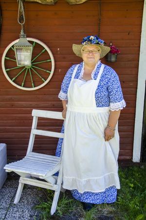 Annelie i vacker klänning och dekorativ hatt.