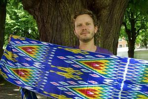 Färdledaren Johnny Friskilä visar upp siden från centralasiatiska Buchara.