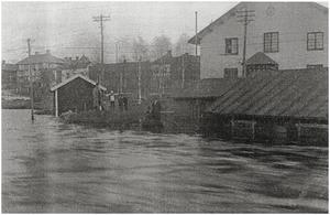 Falu valskvarn sedd från Magasinsbron Bebyggelse vid Slaggatan i bakgrunden. Vattenpumpen skymtar vid stolpen t.v.