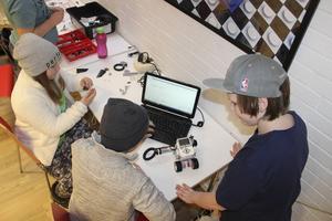 Rasmus Söderberg, Elin Johansson och Niklas Nilsson och Fredrik Israelsson bestämmer hur roboten ska agera med hjälp av ett datorprogram.