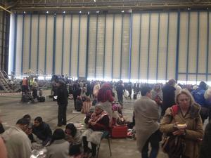 Resenärer på flygplatsen Zaventem i Bryssel har evakuerats till en hangal strax utanför flygplatsen. I skrivande stund väntar de på besked om när de kan få lämna platsen.