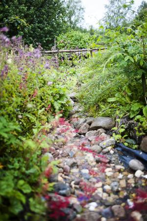 Den konstgjorda bäcken porlar stilla ned igenom trädgården.