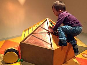 Tvååringen Axel från Utanby förskola i färd med att klättra.
