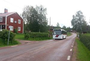 Bussen rullar tillbaka in i Åsen och stannar vid stolpen