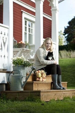 Miriam med katten Hilma i knäet. Den vackra förstukvisten med snickarglädje är nybyggd, men ser ut som den alltid funnits där. Familjen har utsikt över Siljan från både sovrum och kök.