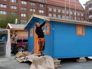 Henric Carlsson (M) målar stugan i partiets färger.