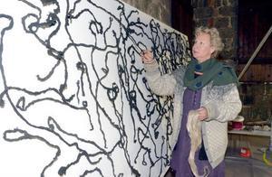 Gabriella Göransson hittade en bit linfiber i Verket som hon håller i handen, samma material som hon använder för sin fiberkonst. Fast då maler hon ner fibrerna, färgar och formar dem, innan fäster dem på duken.