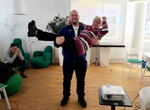Världens just nu starkaste man Fredrik Svensson gör ett lyft. Ruth Trapp låter sig gärna lyftas. Dagbladets sportchef Oskar Lund beskådar i bakgrunden.