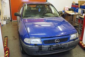Männens bil saknar främre registreringsskylt. Den bakre registreringsskylten är tillverkad av en bit vit kartong där bokstäver och siffror är skapade med svart vävtejp.