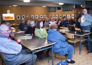 Olle Berglund, ordförande i Kommunbygderådet i Ovanåkers kommun, leder mötet i bygdegården i Svabensverk inför ett 40-tal personer.