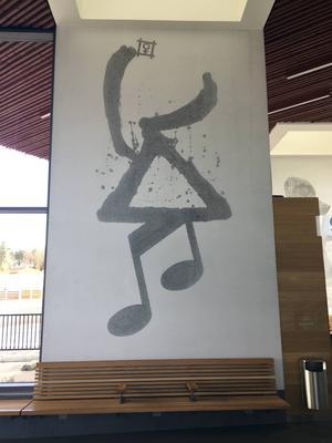 En dansande figur med älghorn och en musiknot som ben, signerad Modhir Ahmed.