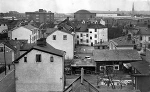 Ängsgärdet 1954. Sumpen kallades stadsdelen vid den här tiden, eftersom en stor del av fastigheterna tilläts förfalla i väntan på kommunens framtida planer för Ängsgärdet. Bilden är tagen från öster, från Baldersgatan. I bakgrunden syns Svenska Metallverken och Domkyrkan.