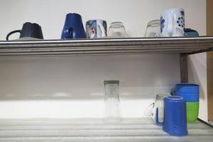 Här förvaras glas och muggar, på hyllor med plastbrickor.
