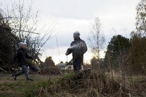 Kim Broman vattnar marken inför tändningen av Färilas största brasa. Neo Carlström rusar till för att hjälpa.