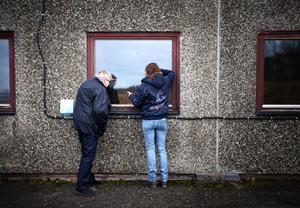 Eva Olsson och Anita Wennersten tittar in genom fönstren till den numera stängda fabrikslokalen.