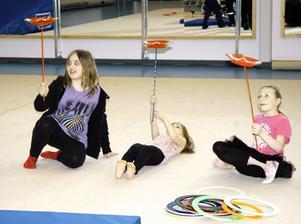 Liggande tallriksnurr. Ida och Lina Lind, och Alice Norén, testar att lägga sig ner medan de snurrar tallrikar.