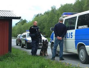Här har polisen gripit misstänkt nummer två men letar fortfarande med hundpatruller och helikopter i omgivningarna kring Hållands folkhögskola efter den tredje. Den förste sitter i en av polisbilarna.