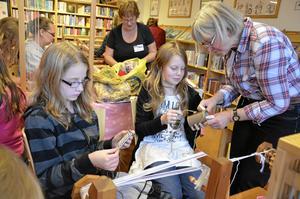 Ingrid Thorin från Fjugesta vävstuga visar Ella Edlund och Felicia Andersson hur man får väven tät med hjälp av en kam.