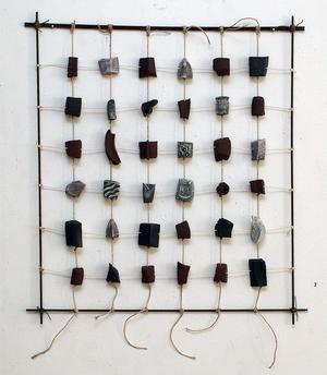 I en smal ram hänger små keramikbitar som alla har växtmotiv.