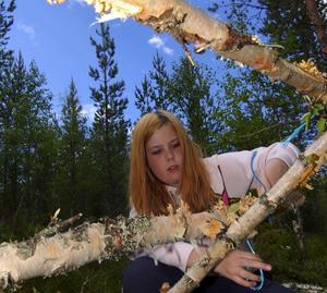 Bygga vindskydd. Janina Värme knyter ihop björkstammarna.