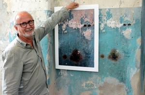 Björn Engström visar var han tänkt hänga ett av de fotografier han tagit i utställningslokalen i Bryggeriet.