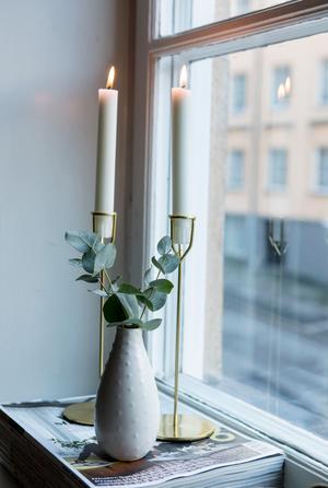 En tidningstrave, ett par ljusstakar och en vas bildar ett fint stilleben.