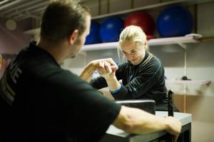 Karolin Andersson segdrar mot Daniel Engström på brytbordet i gymmet på Östbergsskolan där styrka och teknik tränas upp.
