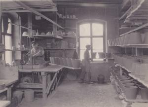 Drejskivorna drevs under många år av vattenkraft från en bäck vid fabriken. På bilden drejas blomkrukor under tidigt 1920-tal.