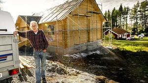Stig Jönsson bygger en timmerstuga liknande den som brann ned. Till höger i bild syns den röda stugan som klarade sig i skogsbranden.