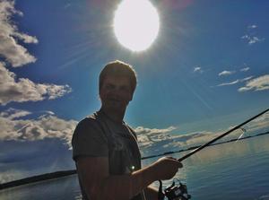 Det var en av få soliga dagar denna sommar och sonen Johan fiskar från vår båt. Jag fick upp mobilen och tog en bild rakt mot solen.Såg ingenting när jag knäppte på grund av solen. Men bilden blev riktigt bra.