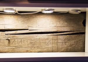 Delen av den gamla träväggen där inskriptionerna hittades ramas in av en hylla.
