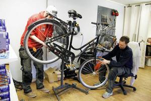 Stefan Källman som driver Cykelverkstaden och Anders Bergdal byter slang på grund av en punktering.