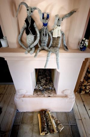 Spismuren är milt rosafärgad genom hela stugan. I rummet på nedervåningen visar Stina skinn och andra produkter som fåren bidrar med. Ovanpå spisen sitter några djur i tovad ull.
