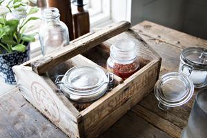 Återbruk i flera steg. Den gamla sockerlådan hade byggts om för att förvara spik i båthuset. Nu står den på matbordet med olja och kryddor.