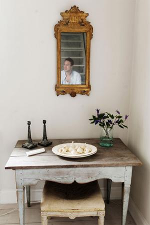 Detta bord har aldrig varit övermålat utan har stått på en släktgård i 200 år. Den är gjord vid sekelskiftet och benen är gustavianska. Men underredet har en svängd svängd rokokoform. Snickaren har inspirerats av rokoko men det är gustavianskt. Det är inte något som man skulle ha gjort i Stockholm utan det är ett provinsarbete.Taburetten och spegeln är båda gustavianska. På bordet står ett flintgodsfat och gustavianska tennljusstakar och ett gammal syltburk agerar vas.