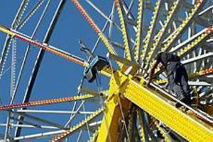 Foto: LASSE WIGERT Utan skyddsnät. Feststämningen skjuter i höjden i Gävle. Det gäller att grabbarna som monterar ihop Pariserhjulet håller tungan rätt i mun.