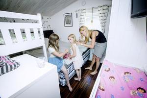 Isabell, Natalie och mamma Ann i sommarstugans sovrum. Än så länge ryms hela familjen där.