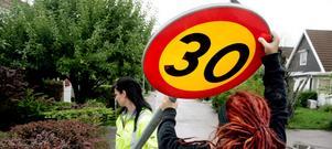 Ulrika Törngren och Emma Andersson sätter upp en ny skylt om hastigheten i ett bostadsområde på Bäckby.