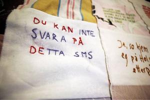 Ett lapptäcke med broderade SMS-meddelanden. Lapptäckets broderier innehåller allt från komiska till vardagliga meddelanden, kärleksbrev och sorgliga besked.
