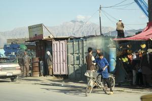 Sol över Kabul. Hindukuschmassivet utgör kuliss till Kabuls stadsbild. Här på Jalalabad Road pågår det vanliga livet för afghanerna i stort och smått.