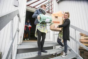 MIkaela Lindström och Elina Bergström bär ut de sista grejerna efter auktionen på Folkets hus i Sveg