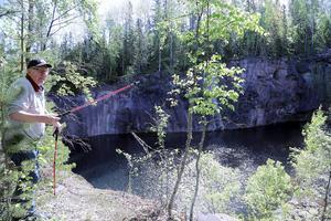 Arvid Vestin visar det stora gruvhålet med dess branta väggar. Här jobbade han för 50 år sedan.
