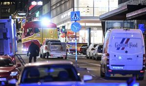 Strax efter midnatt var bärgare på plats vid den kapade lastbilen (t h) som står inkörd i Åhlens butik på Drottninggatan i Stockholm.
