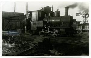 Ett foto från 1920-talet och visar ett av de mindre ånglok som skötte transporterna på den smalspåriga industrijärnvägen inom dåvarande Domnarvets järnverk. I bakgrunden kan man skymta gamla sinterverket som numera är rivet.