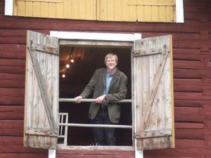Kenth Olsson kikar ut från Mälteriet i Växbo kvarn där han ställer ut sina tavlor med hälsingemotiv.