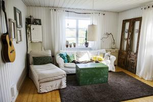 Vardagsrummets har målats vitt och grenar tar plats både i vaser och som gardinstänger.